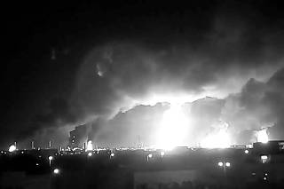 Fires burn in the distance after a drone strike by Yemen's Iran-aligned Houthi group on Saudi company Aramco's oil processing facilities in Buqayq