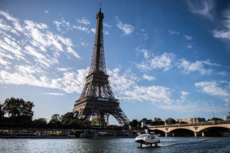 Barco elétrico atravessoa o rio Sena com a torre Eiffel ao fundo em um dia ensolarado com algumas nuvens
