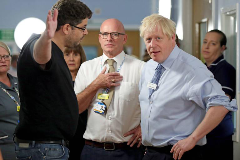 O primeiro-ministro britânico, Boris Johnson, à dir., é confrontado por pai de recém-nascida em hospital em Londres