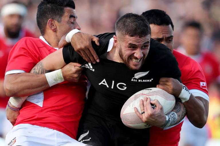 TJ Perenara, dos All Blacks, é agarrado por jogadores de Tonga durante amistoso