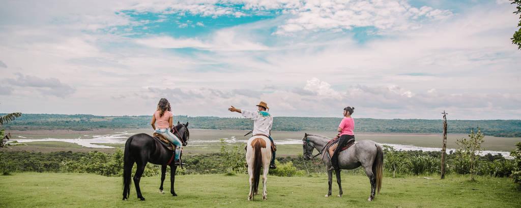 Fábio da Garota (centro) conduz duas turistas até um vale, todos a cavalo
