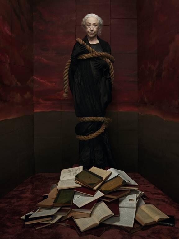 A atriz Fernanda Montenegro vestida de bruxa e cercada por uma fogueira de livros