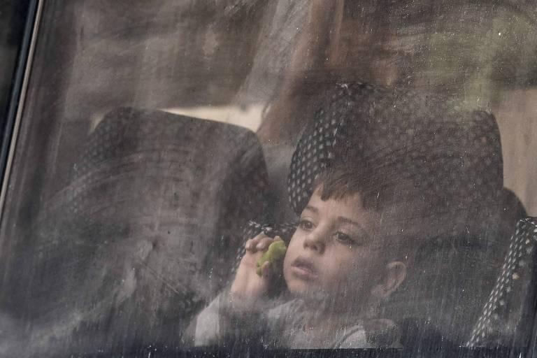 Menino olha pela janela de ônibus