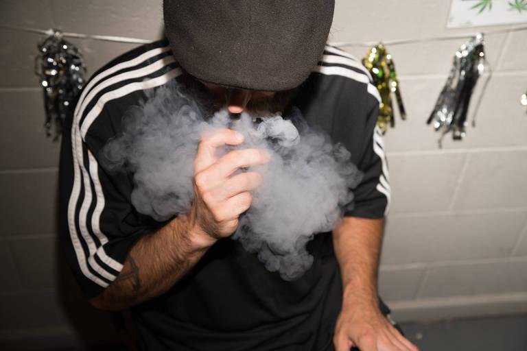 Homem fuma com cigarro eletrônico