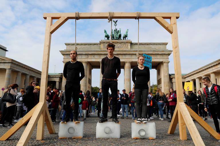 Três pessoas vestidas de preto estão em cima de blocos de gelo e sob uma forca