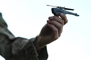 Britain's Prime Minister Boris Johnson is shown a Black Hornet nano drone by a member of the military during a meeting with military personnel on Salisbury plain training area near Salisbury