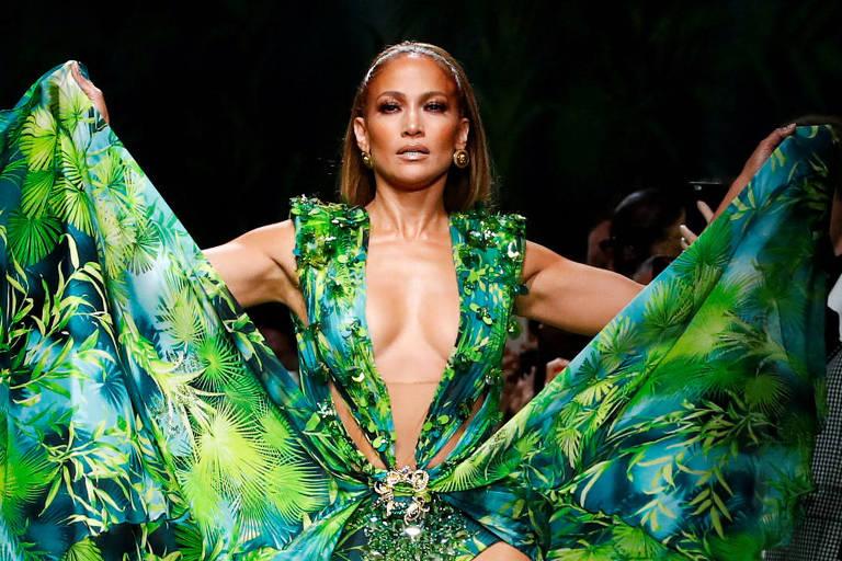 Jennifer Lopez desfila para Versace na Semana de Moda em Milão, com vestido verde decotado até a altura da barriga, de ombros abertos