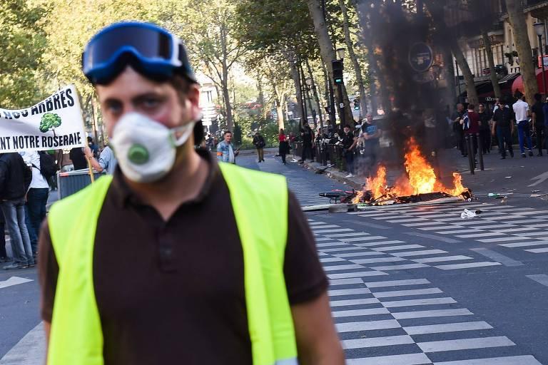 """Manifestante dos """"coletes amarelos"""" em frente a motocicletas incendiadas durante confronto com a polícia, em Paris"""