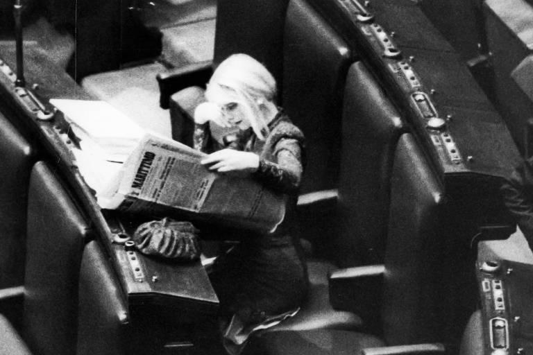 Mulher lendo jornal sentada em uma fileira de cadeiras