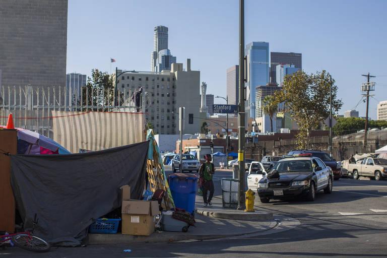 Policial abordam homem em rua do Skid Row, ao lado de barraca de moradores de rua, em Los Angeles