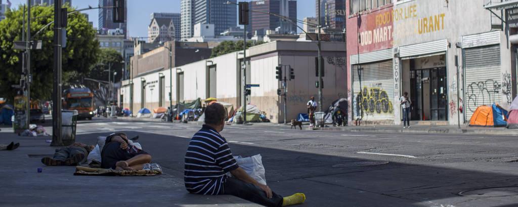 Moradores de rua no Skid Row, com prédios do centro financeiro de Los Angeles ao fundo