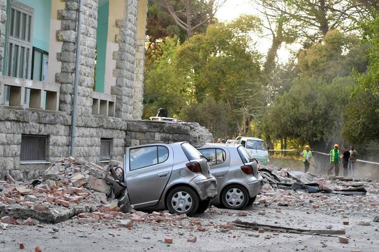 Veículos são atingidos por destroços do edifício em Tirana enquanto funcionários limpas a frente do prédio após tremore