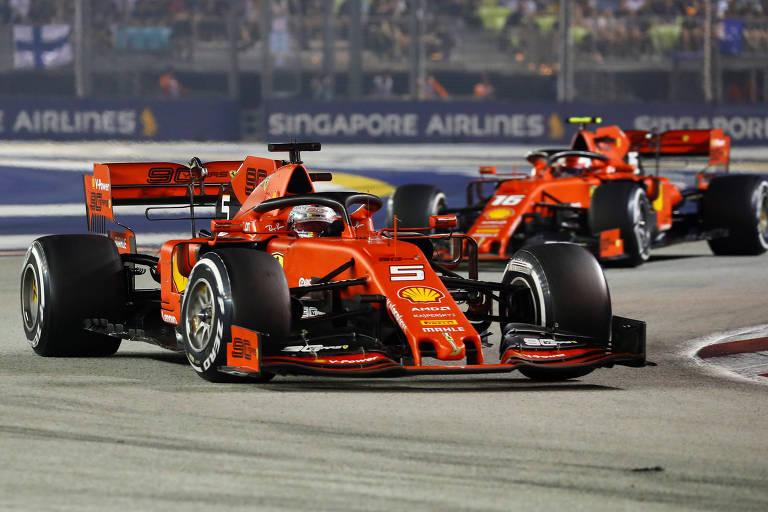 Carros de Fórmula um da mesma equipe, a Ferrari, na cor vermelha com detalhes amarelos. Foto tirada durante a corrida, os carros estão passando por uma curva.