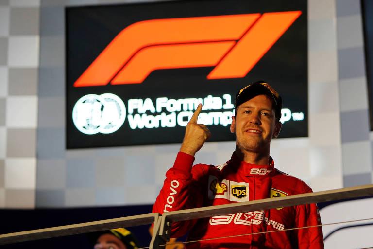 Em frente a placar luminoso, piloto de macacão vermelho e boné preto faz o sinal de número 1 com o dedo