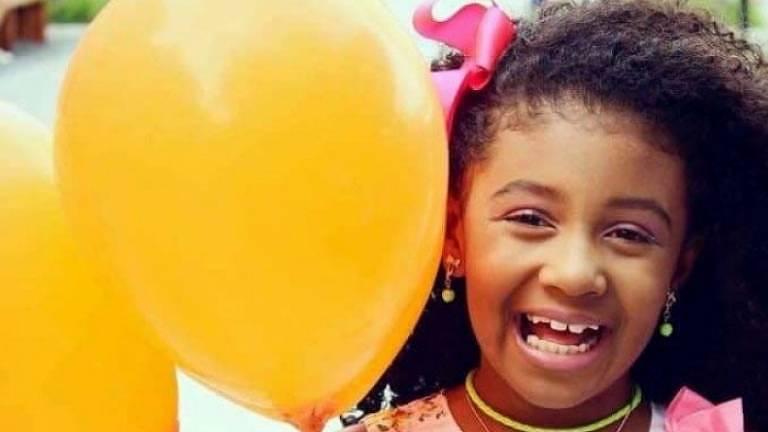 Menina de vestido de flores segura dois balões amarelos