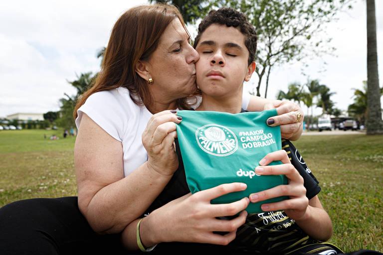 Nickollas Grecco recebe o carinho da mãe, Silvia, que narra os jogos Palmeiras para o filho deficiente visual; dupla concorre a prêmio da Fifa