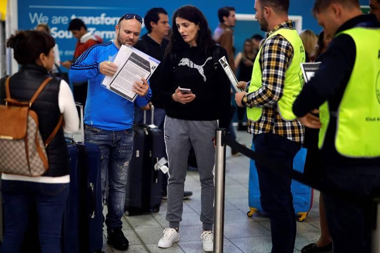 Oficiais conversam com passageiros que foram afetados pela falência da Thomas Cook