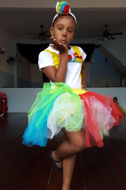 Uma menina de pele negra está vestida de saia colorida, de tule, e com um arquinho também colorido na cabeça, joga um beijo para câmera