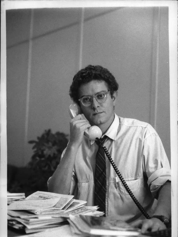 retrato em preto e branco de homem vestindo camisa e gravata sentado em uma escrivaninha e falando ao telefone