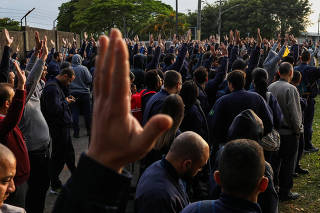 Workers at Brazilian planemaker Embraer raise their hands to vote on starting the strike during an assembly in Sao Jose dos Campos