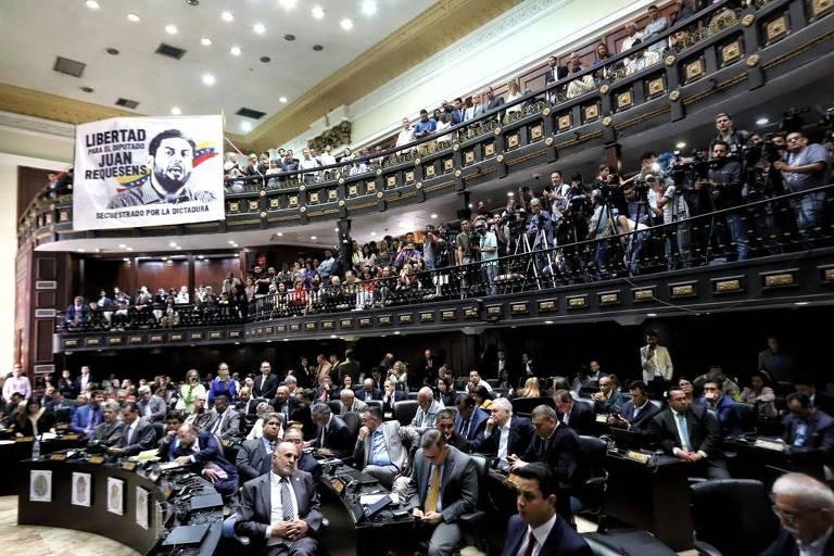 Assembleia Nacional com vários deputados sentados; ao fundo, bandeira pede libertação de um deputado preso