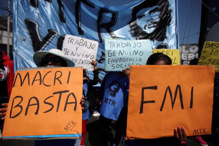 Manifestantes seguram duas placas laranjas com a mensagem Macri, basta FMI. Ao fundo, uma faixa com a imagem de Che Guevara