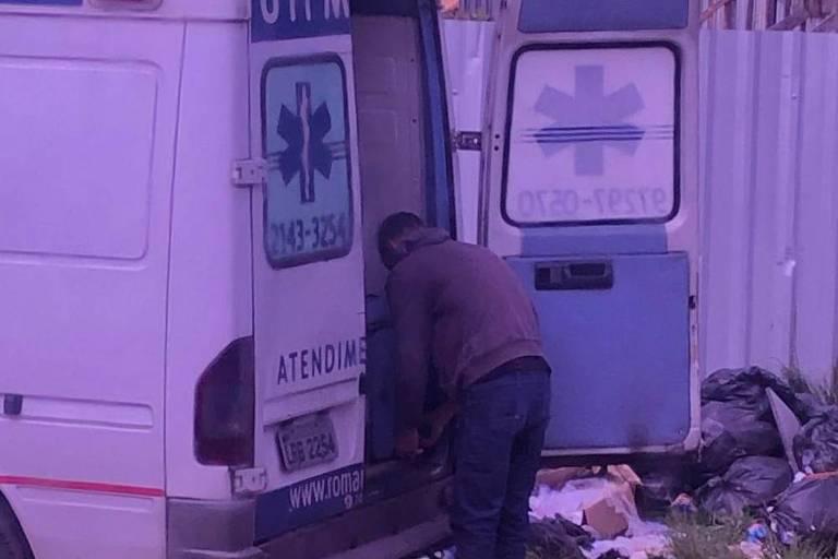 Uma ambulância com uma das portas abertas em frente a um container e a vários sacos de lixo