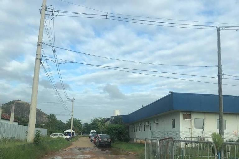 Em uma rua de terra, um container está na lateral direita. Ele é pintada de branco com teto em azul. Há apenas uma porta de saída
