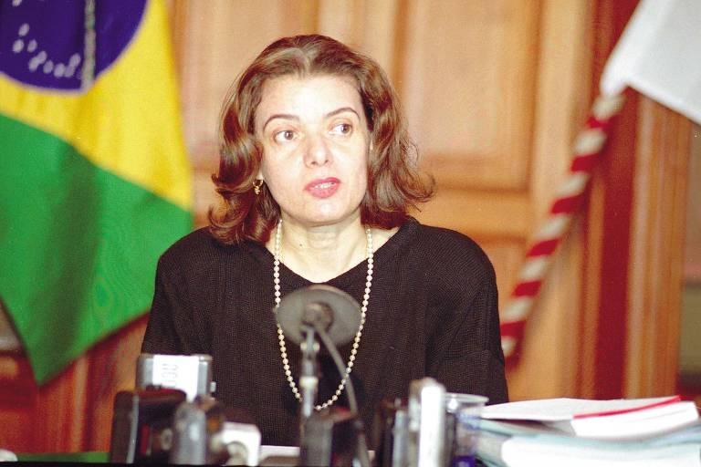 Vestindo preto e um colar elegante, Carmen Lúcia discursa com bandeira do Brasil ao fundo.