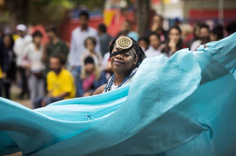 Mulher negra com saia azul dança, enquanto público assiste ao fundo