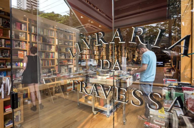 """Porta de vidro com """"livraria da travessa"""" escrita e loja por dentro"""