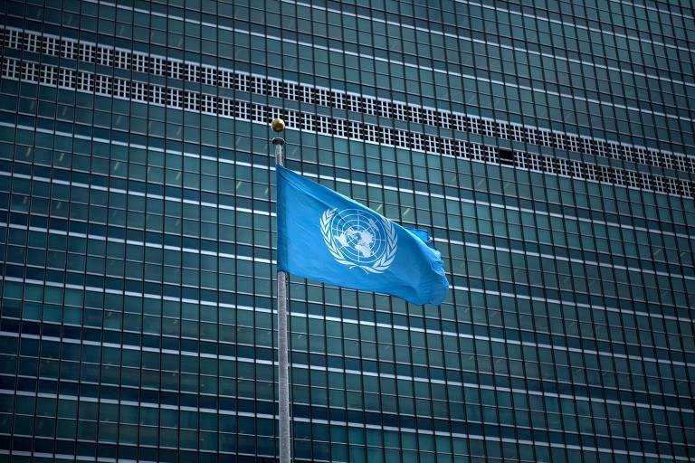 A bandeira da ONU de cor azul está hasteada em frente a um prédio.