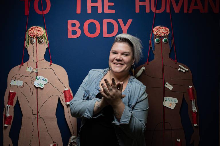 Mariana está sorridente na frente de um quadro que retrata partes do corpo humano
