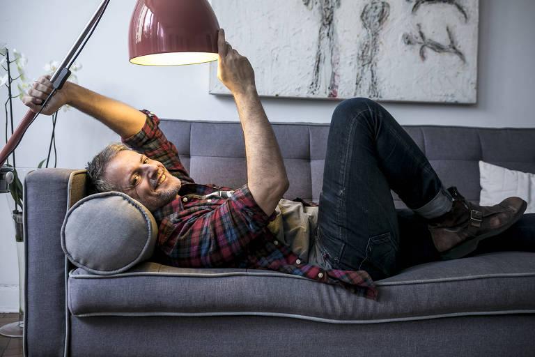 Homem deitado em sofá com luminária