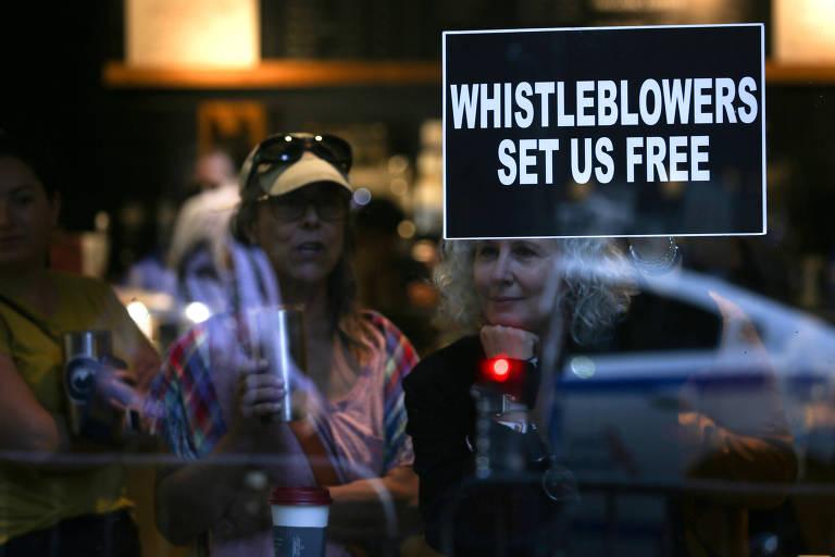 """Mulher segura cartaz em que se lê """"denunciantes anônimos nos libertaram"""" em café próximo a evento de campanha de Donald Trump, em Nova York"""