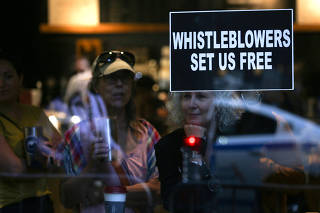A woman holds a sign about whistleblowers in a cafe near U.S. President Trump?s motorcade as he attends a campaign fundraiser nearby in New York