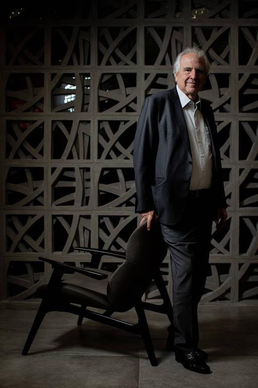 Empresário veste camisa branca e paletó azul marinho e posa, em pé, em frente a uma parede de concreto vazado