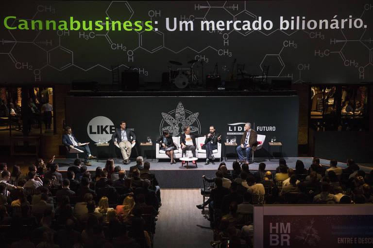 """Evento com pessoas sentadas em palco; acima delas frase """"cannabusiness: um mercado bilionário"""""""