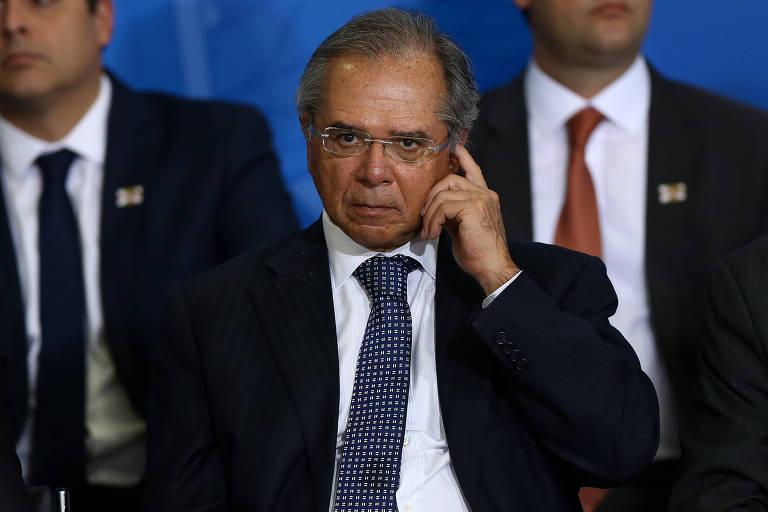 O ministro Paulo Guedes da Economia, aparece olhando para frente, coçando a lateral da cabeça com o dedo indicador
