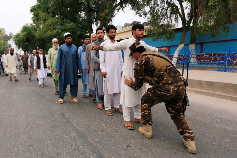 Membro das forças de segurança do Afeganistão revista eleitor em Jalalabad, neste sábado (28)