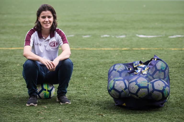 Mulher agachada em gramado, com bolsa de bolas ao lado