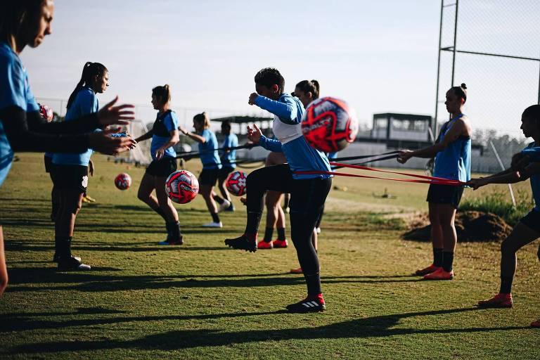 Mulheres em gramado com bola de futebol