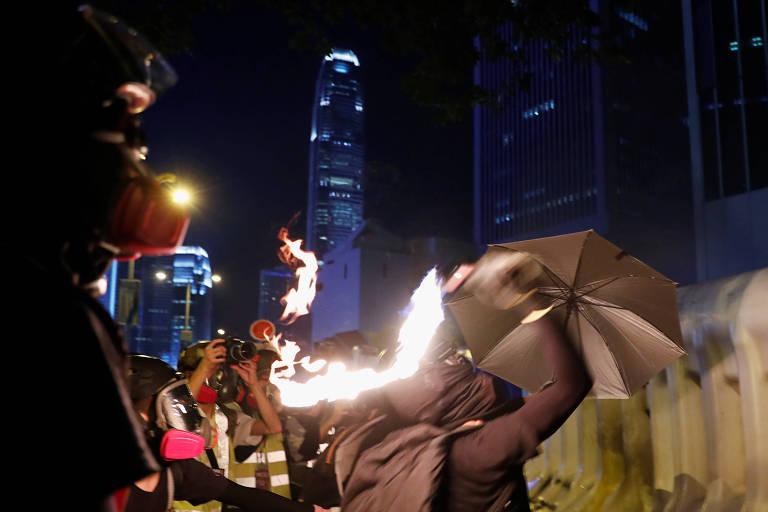 Manifestante atira coquetel molotov durante protesto em Hong Kong, neste sábado (28)