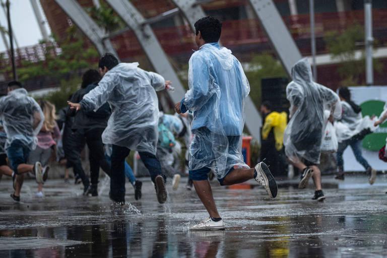 Pessoas correndo usando capas de chuva na abertura dos portões do Rock in Rio 2019
