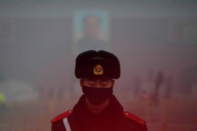 Policial na praça Tiananmen, em Pequim, coberta pela fumaça da poluição, em foto de 2016