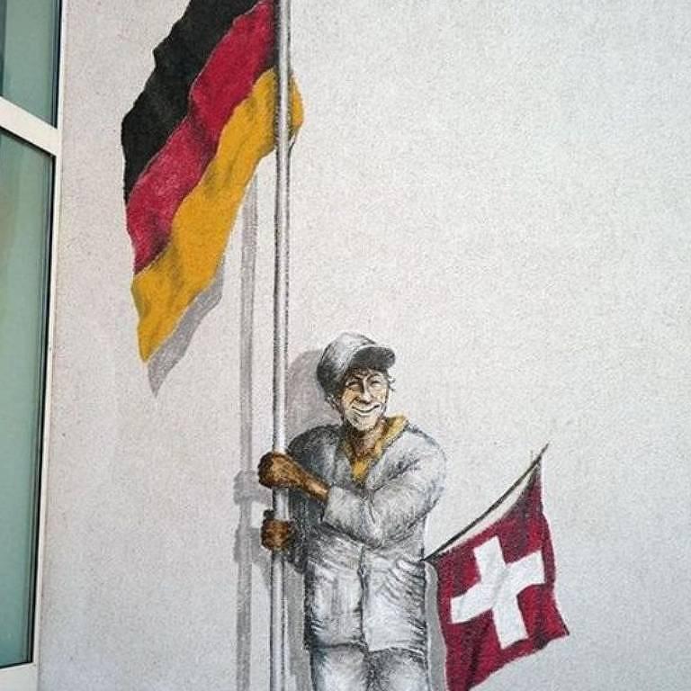 A Trilha do Enclave (ou Exclave) inclui 11 paradas em Büsingen, como esse mural de um homem segurando uma bandeira alemã e uma suíça