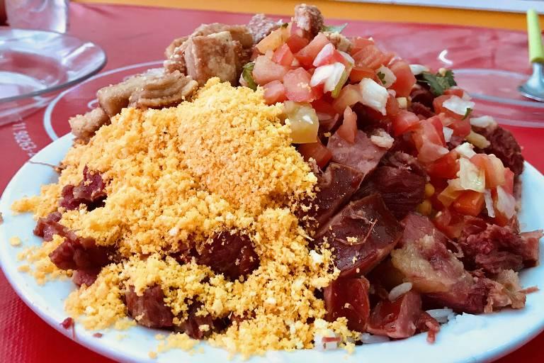 Servido na Casa do Norte Sol Nascente, o Arrumadinho é um prato composto por feijão de corda, carne do sol, arroz torresmo, linguiça calabresa, farofa e vinagrete
