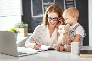 Businesswoman mother  woman with toddler working at computer