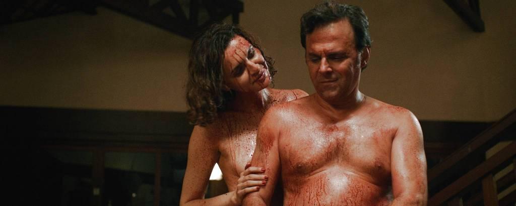 Uma mulher e um homem conversam nus e com sangue espirrado em seus corpos
