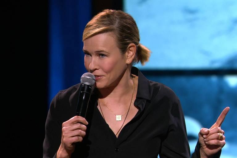 mulher loira fala no microfone durante uma apresentação